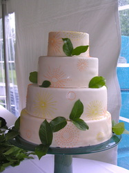 Bright suns and lemon leaves on fondant wedding cake. Raleigh, NC