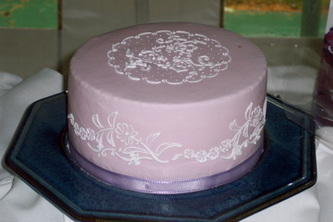 Single tier fondant wedding cake decorated with a floral royal icing stencil. Hillsborough, NC