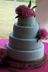 Smooth fondant wedding cake decorated with bright peonies. Durham, NC